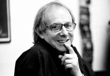 Portrait of Ken Loach smiling and pointing to his mouth