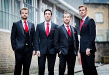 Four men in smart suits with red ties and pocket squares. They are supposed to all be looking at something in sky for this shot, but one of them is looking at the camera.