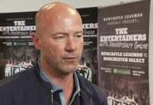 Alan Shearer in front of posters for The Entertainers 20th Anniversary Game