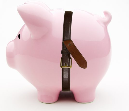 A piggy bank with a leather belt around its waist.