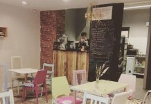Interior of Wildflower cafe. Brightly painted, reclaimed furniture and a small bar next to a blackboard menu.